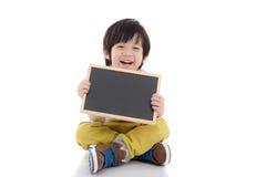 Азиатский мальчик держа черную доску на белой предпосылке изолированный Стоковое фото RF