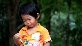 Азиатский мальчик ест очень вкусное пирожное на парке видеоматериал