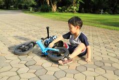 Азиатский мальчик играя около его велосипеда Стоковые Изображения