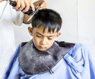 Азиатский мальчик имея стрижку. Стоковое Фото