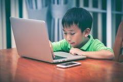 Азиатский мальчик наслаждаясь современный играть технологий поколения крытый Стоковые Фотографии RF