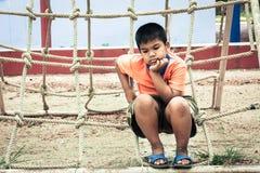 Азиатский мальчик сидя самостоятельно на спортивной площадке стоковые фотографии rf