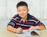 Азиатский мальчик счастливый с его домашней работой Стоковое фото RF