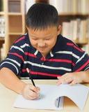 Азиатский мальчик счастливый с его домашней работой Стоковое Фото