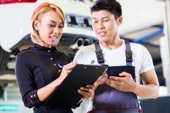 Азиатский механик и менеджер автомобиля задавая задачи стоковая фотография