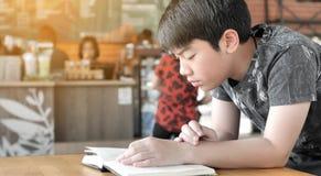 Азиатский милый мальчик прочитал книги пока ждущ их матерей для покупки напитков в кафе стоковое фото