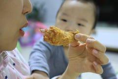 Азиатский младенец видя, что мать съела жареную курицу с завистливым глазом стоковые изображения