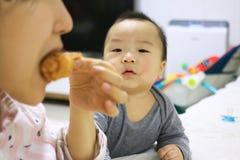 Азиатский младенец видя, что мать съела жареную курицу с завистливым глазом стоковые фото