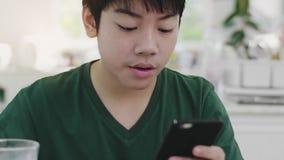 Азиатский молодой мальчик используя перечени через применения смартфона, пока медленно ест органический завтрак молока акции видеоматериалы