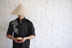 Азиатский молодой послушник на белой кирпичной стене стоковое фото