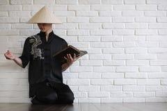 Азиатский молодой послушник на белой кирпичной стене стоковые изображения rf
