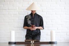 Азиатский молодой послушник на белой кирпичной стене стоковое изображение rf