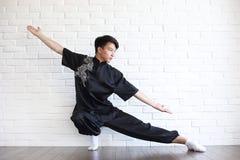 Азиатский молодой послушник на белой кирпичной стене стоковое фото rf