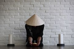 Азиатский молодой послушник на белой кирпичной стене стоковые изображения