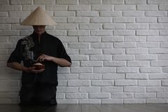 Азиатский молодой послушник на белой кирпичной стене стоковые фотографии rf