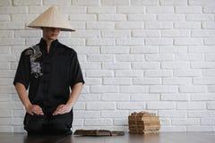 Азиатский молодой послушник на белой кирпичной стене стоковая фотография