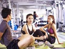 Азиатский молодой человек и женщины отдыхая во время тренировки Стоковые Изображения