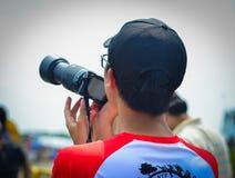 Азиатский молодой человек наблюдая плоское шоу стоковое изображение rf