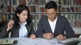 Азиатский молодые человек и женщина пар обсуждая долевую диограмму в библиотеке сток-видео