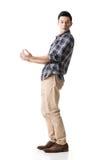 Азиатский молодой парень носит или принимает что-то стоковая фотография