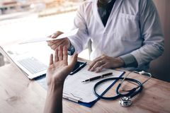 Азиатский мужской доктор говоря в комнате клиники и вручая рецепт к пациенту стоковые изображения rf