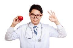 Азиатский мужской знак О'КЕЙ выставки доктора с яблоком Стоковая Фотография RF