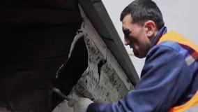 Азиатский мужской лейборист в оранжевом равномерном жилете ломает грязную старую деревянную стену акции видеоматериалы