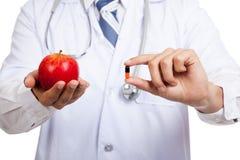 Азиатский мужской доктор с яблоком и капсулой Стоковое Изображение RF