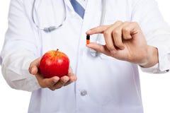 Азиатский мужской доктор с яблоком и капсулой Стоковое фото RF