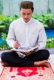 Азиатский мусульманский человек изучая Koran или Коран стоковые изображения