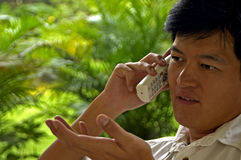 азиатский мыжской говорить телефона Стоковое фото RF