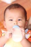 Азиатский младенец и имеет бутылку молока в руке Стоковое Изображение