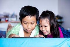 Азиатский наблюдать детей видео- и играть игру на цифровой таблетке стоковое изображение