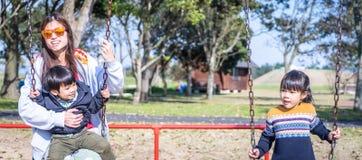 Азиатский наслаждаться семьи качания в парке Стоковая Фотография RF