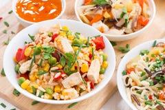 Азиатский обед - жареный рис с тофу, лапши с овощами стоковое фото