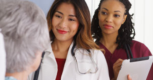 Азиатский доктор и медсестра женщины говоря к пожилому пациенту в кровати Стоковые Фотографии RF