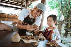 Азиатский отец и дочь работая с глиной стоковое изображение rf