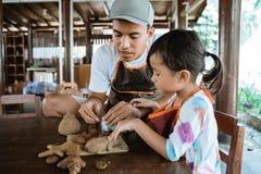 Азиатский отец и дочь работая с глиной стоковые изображения