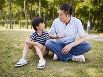 Азиатский отец и сын имея переговор стоковые фото