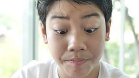 Азиатский положительный черный ребенок сидит на windowsill и выпивает горячий шоколад, акции видеоматериалы