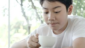 Азиатский положительный черный ребенок сидит на windowsill и выпивает горячий шоколад видеоматериал