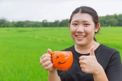 Азиатский предназначенный для подростков тучный большой палец руки улыбки женщин поднимающий вверх и кружка владением Стоковые Изображения RF