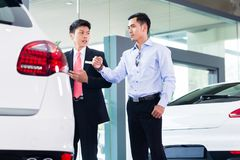 Азиатский продавец автомобилей продавая автомобиль к клиенту Стоковое Изображение