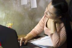 Азиатский работник женщины страдая от повреждения, усталости, боли на шеи, мышце, усилил во время работать с ноутбуком в течение  стоковое изображение