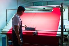 Азиатский работник контролирует ткани в заводе ткани стоковое фото rf