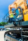Азиатский работник на строительной площадке экскаватора лопаткоулавливателя Стоковые Изображения
