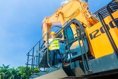 Азиатский работник на строительной площадке экскаватора лопаткоулавливателя Стоковое фото RF