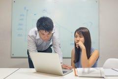 Азиатский работник офиса читая финансовый номер на ноутбуке стоковые фото