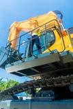 Азиатский рабочий-строитель на экскаваторе лопаткоулавливателя Стоковые Фотографии RF