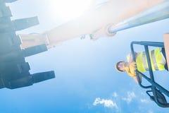 Азиатский рабочий-строитель на экскаваторе лопаткоулавливателя стоковое изображение rf